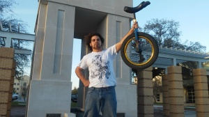 Nicholas Squyres with unicycle by clock 2 tower photo by Rowan Lehr